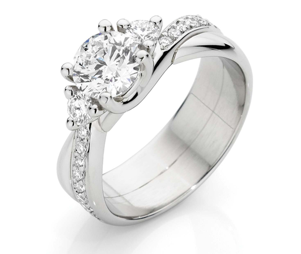 Round trilogy diamond ring with larger centre diamond on a cross over grain set diamond and plain band