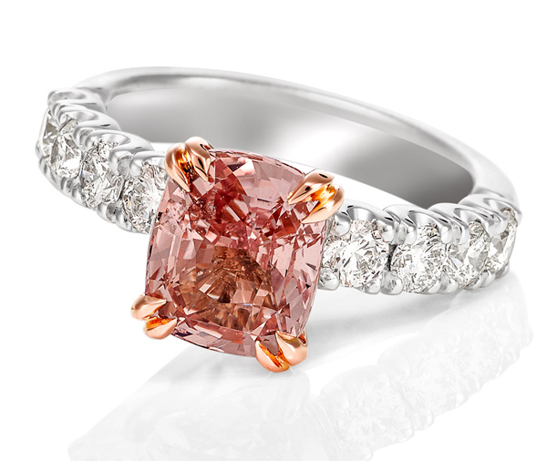 18ct white gold claw set diamond band ring with a rose gold double claw setting featuring a cushion cut Padparadscha Sapphire