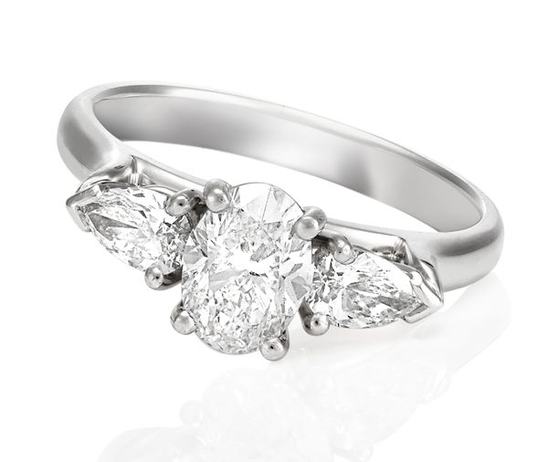 white gold trilogy engagement ring with oval diamond claw set in-between a pair of pear shape diamonds