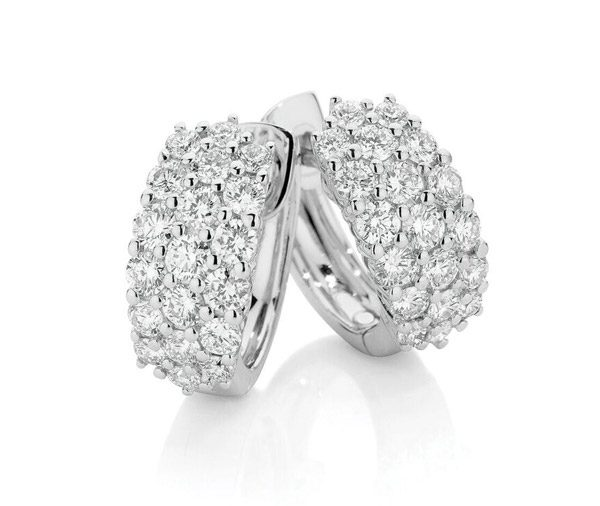 huggie style earrings featuring three rows of claw set round brilliant cut diamonds